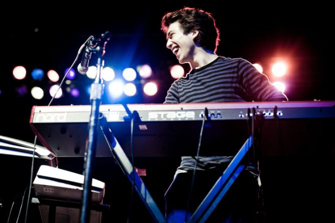 Smiling professional Woman musician Playing a piano Keyboard on a stage. An 88 key keyboard is a full sized keyboard. An adult may want to get started with a 76 key keyboard