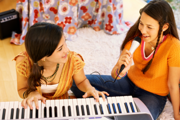 Keyboard Piano for Beginners. Two Young Women Practicing the Keyboard