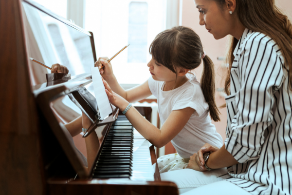 Young girl marking up sheet music during a piano lesson