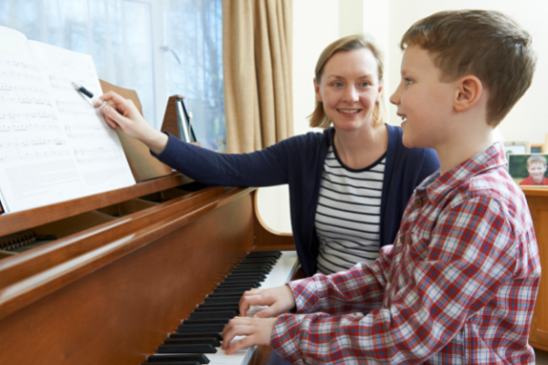 Piano Teacher pointing to Sheet Music