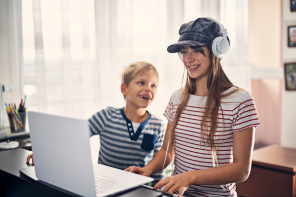 Teens Enjoying themselves. Adolescent girl and boy with piano keyboard and computer
