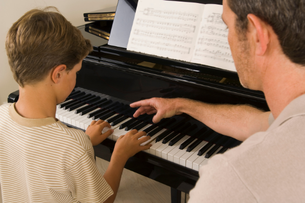 Adult Male having piano lesson with young boy