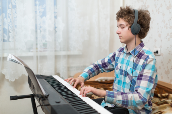Teenage Boy Composing Music on Piano Keyboard.  The Yamaha P71 is good for this purpose.