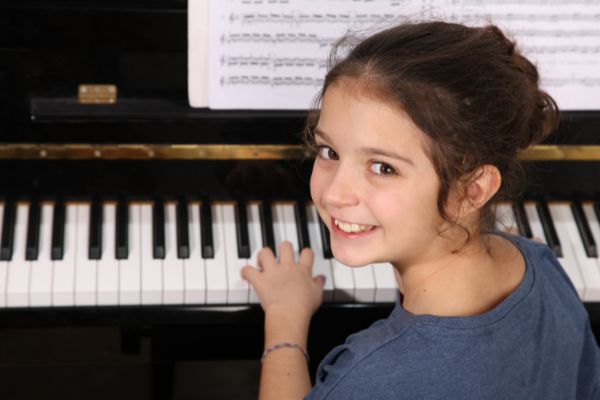 Young Girl in Blue Shirt Practicing Piano